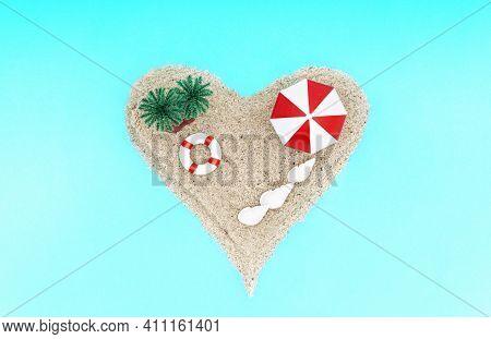 Heart-shaped Miniature Toy Island With Palm Trees, Sun Umbrella, A Lifebuoy And Seashells On A Turqu