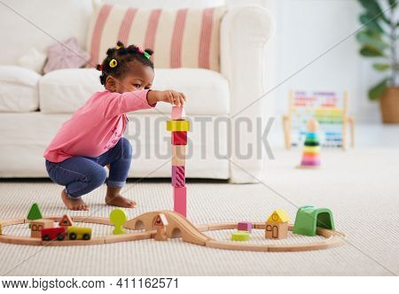 Cute African American Toddler Baby Girl Playing Wooden Toys, Stacking The Tower Blocks On The Carpet