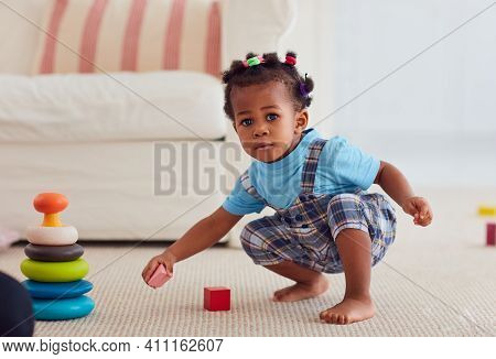 Cute African American Baby Girl Playing Toys At Home