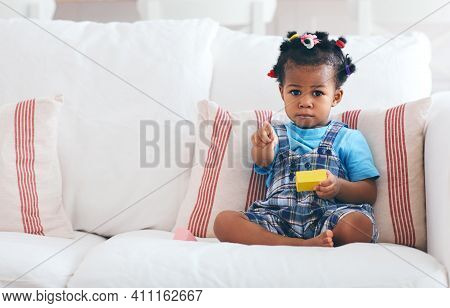 Cute Toddler Baby Girl Sitting At The Cozy Sofa Pointing Finger At You