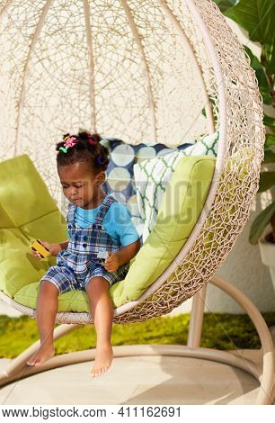 Cute Toddler Baby Girl Sits In A Hanging Rattan Chair At A Sunny Terrace