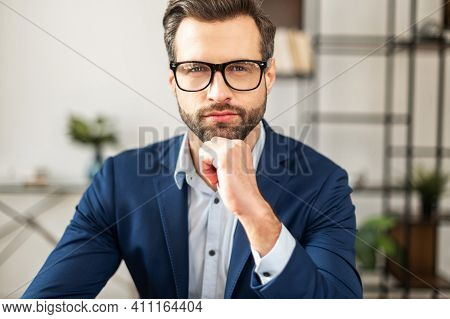 Successful Masculine Businessman In Formal Expensive Suit, Holding Arm Near The Chin, Has A Neat Stu