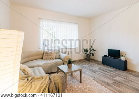 Simply Furnished Living Room In Minimalist Style.room Has Large Corner Sofa With Blankets And Pillow