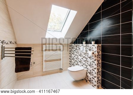 Small Attic Bathroom With Sunroof. The Tiling Is In Brown And Beige Colors Variegated With Texture O