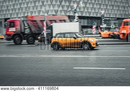 Moscow, Russia - 29.01.2021: Mini Cooper In Motion On Winter City Street. Car Covered By Dirt On Bod