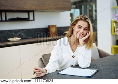 Young Woman Writing Notes In Paper Notebook. Smiling Brunette Young Woman In Casual Doing Notes In D