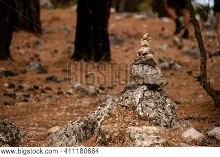 Close-up View On Cairn Marking Hiking Trail In Clearing In Pine Forest