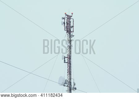 Base Station Mobile Network Antenna On A On The Roof Of A Residential Building Against A Gray Sky. 3