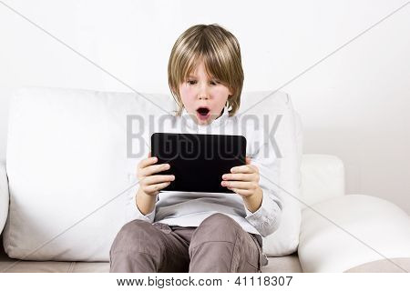 Surprised Blonde Boy With Tablet