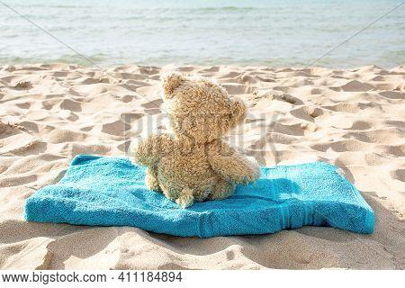 Back View Of Brown Teddy Bear On Aqua Beach Towel On Sand