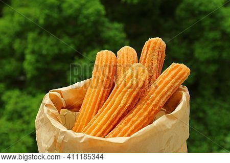 Bag Of Delectable Fresh Fried Churros With Blurry Green Foliage In Background