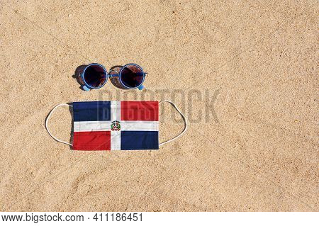 A Medical Mask In The Color Of The Dominican Republic Flag Lies On The Sandy Beach Next To The Glass