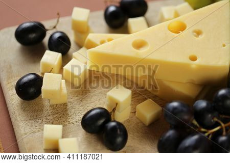 Maasdamer Cheese. Piece Of Cheese Maasdam Or Maasdamer On Wooden Board On Brown Background.hard Chee