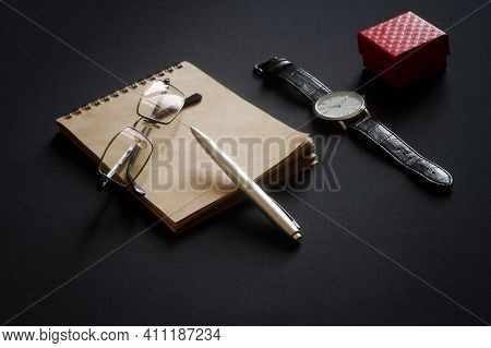 Glasses, A Metal Ballpoint Pen, An Eco-friendly Notebook, A Wristwatch And A Red Box Lie On A Black