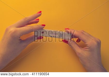 Test For Coronavirus On An Orange Background. Medical Analysis. Girl With Bright Red Manicure Holdin