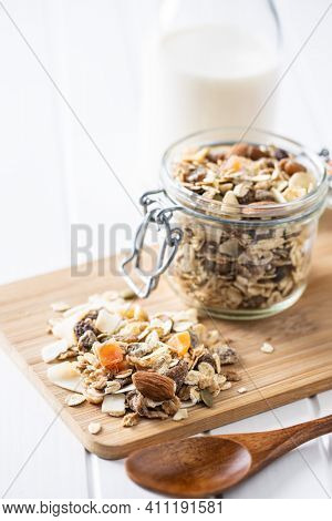 Beakfast cereals on cutting board. Healthy muesli with oat flakes, nuts and raisins