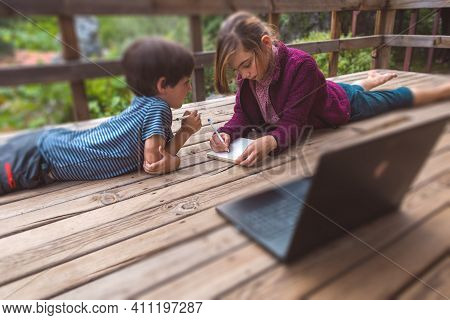 Brother And Sister Are Doing Homework While Sitting On The Veranda Of A House, A Girl Helps Her Litt
