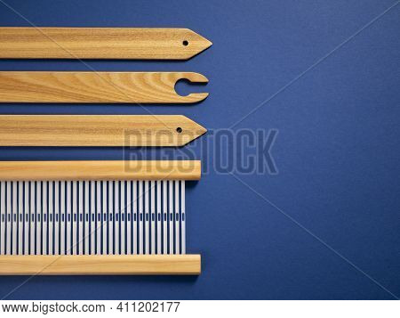Weaving Accessories On The Blue Background With Copy Space. Shuttle, Reed And Shed Sticks