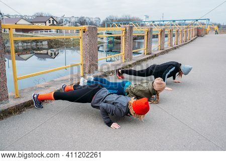 Group Fitness Workout Classes Outdoors. Organized Gym Classes Set Up In Public Parks. Three Women Tr