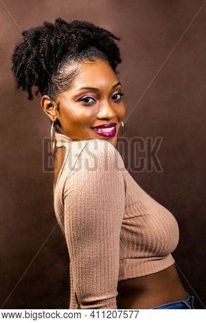 Black Woman Smiling And Posing In A Brown Sweater