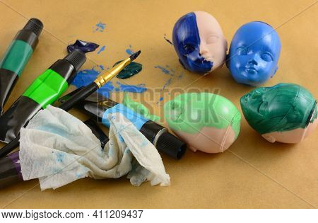 Painting Doll Heads With Acrylic Paint Tubes, Paintbrush And Rag On Parchment Paper