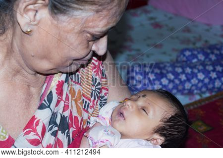 Newborn Little Baby Boy Falling Asleep Lying On His Old Grandmothers Lap. Toddler Great Granddaughte