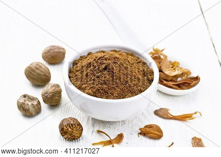 Nutmeg Round In Bowl And Mace In Spoon On Board