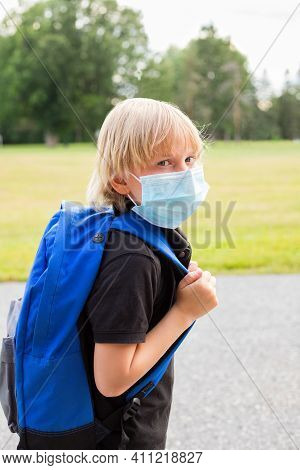 Child In Mask With Blue Backpack At School Yard During Corona Virus.