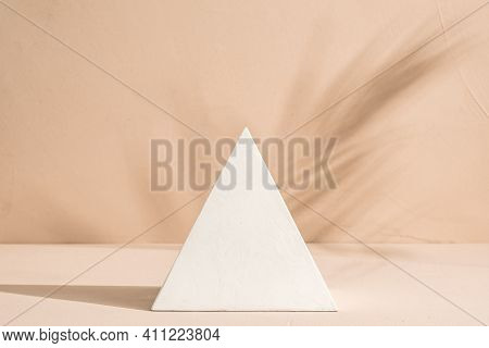 Gypsum Pyramid In Sunlight And Palm Leaf Shadow On Clay Wall Background.