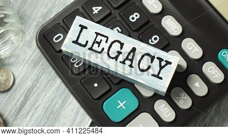 Word Legacy On Wooden Block On Calculator With Shadow. Last Will Heritage Concept.