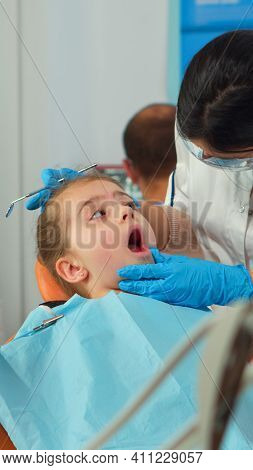 Pediatric Dentist Treating Teeth To Little Girl Patient In Clinic Lying On Stomatological Chair With