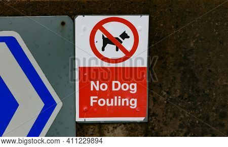 A Rectangular No Dog Fouling Sign In White Black And Red On A Wall.
