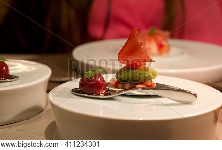 Strawberry Delicacy And Lemon - French Basil On White Plate. Nighttime Atmosphere In A Restaurant Wi
