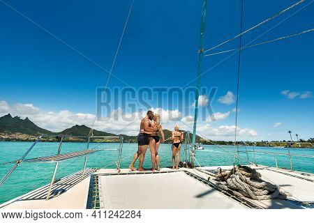 A Happy Family In Swimsuits Stands On A Catamaran In The Indian Ocean. Portrait Of A Family On A Yac