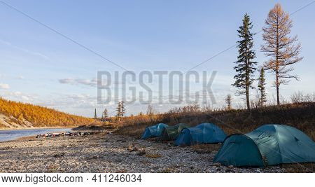 Campground For Tourists And Fishermen On The Rocky Shore Of The Northern River In Autumn. Four Green