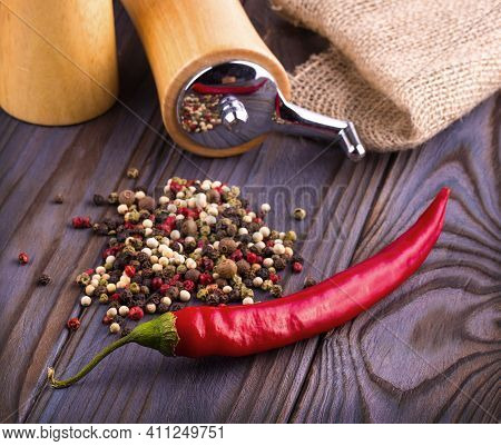 Black Pepper Corns, Red Hot Chili Pepper And Black Pepper Powder On Wooden Background.