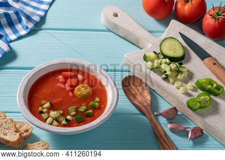 Gazpacho Andaluz is an Andalusian tomato cold soup from Spain with cucumber, garlic, pepper on light blue background