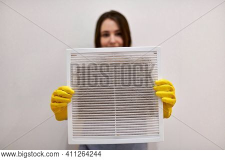Woman Holds Ventilation Grill With Dust Filter To Clean It. Extremely Dirty And Dusty White Plastic,