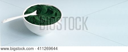 Banner Spirulina Powder In A White Bowl With A Teaspoon On A Blue Background With Place For Text. He