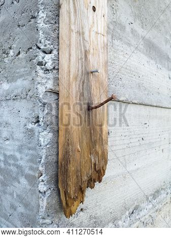 Cement Wall Corner With Old Wooden Plank And Two Rusty Nails. Side View Of Grunge Wooden Board On Br