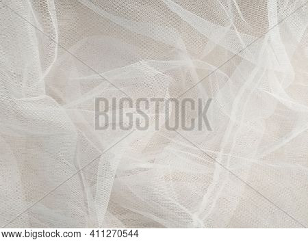 White Mosquito Net Fabric Texture With Folds. Wavy Chiffon Background. Full Frame Of Crumpled White