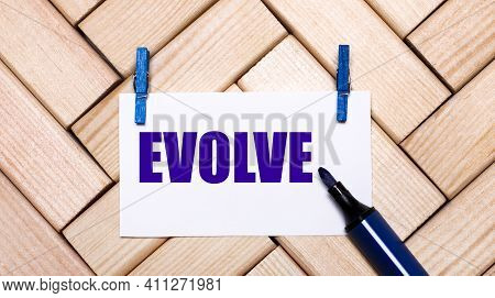 On A Wooden Background, A White Card With The Text Evolve On Blue Clothespins And A Blue Marker. Vie