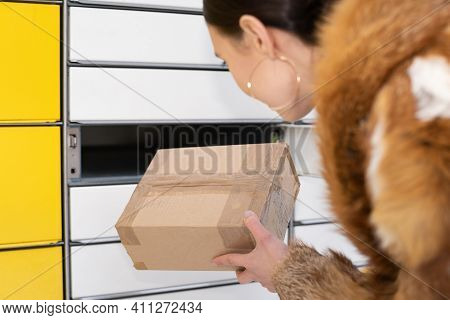 A Rich Woman In A Fur Coat Receives A Package From The Parcel Locker Gently Bending Down. Automatic