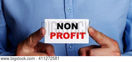 The Words Non Profit Is Written On A White Business Card In A Man's Hands. Business Concept