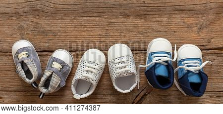 Baby Boy Blue Shoes Variety On Wooden Background, Top View