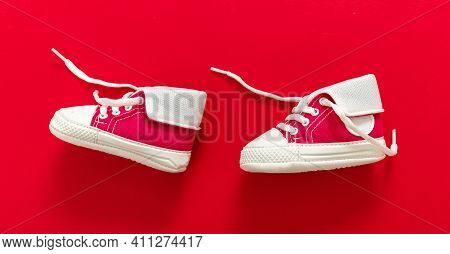 Baby Shoes On Red Color Background, Closeup