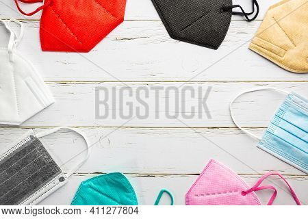 Multicolored Surgical Masks On White Background, Top View. Disposable Medical Face Masks In Differen