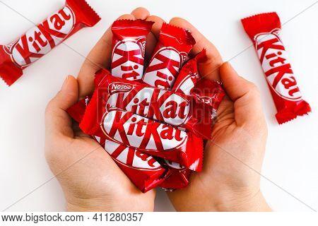 Tambov, Russian Federation - January 30, 2021 Woman Palms Full Of Kitkat Candies By Nestle. White Ba