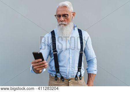 Senior Man Using Mobile Smartphone And Listening Music With Wireless Earphones - Fashion Elderly Mal