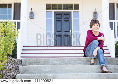 Pensive Attractive Chinese Woman Sitting On Her Front Porch.